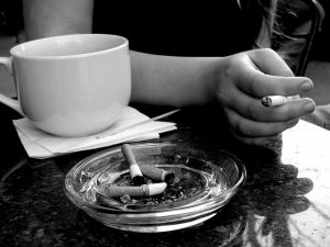 Picture of a hand holding a cigarette next to a cup of coffee.