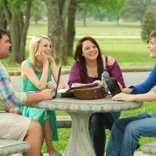 Students having a discussion in the green areas of campus.